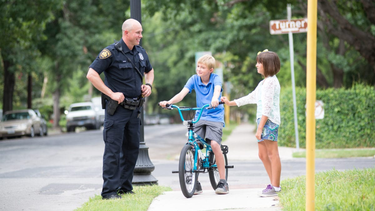 Police officer on the streets talking to a boy on his bike and a little girl.