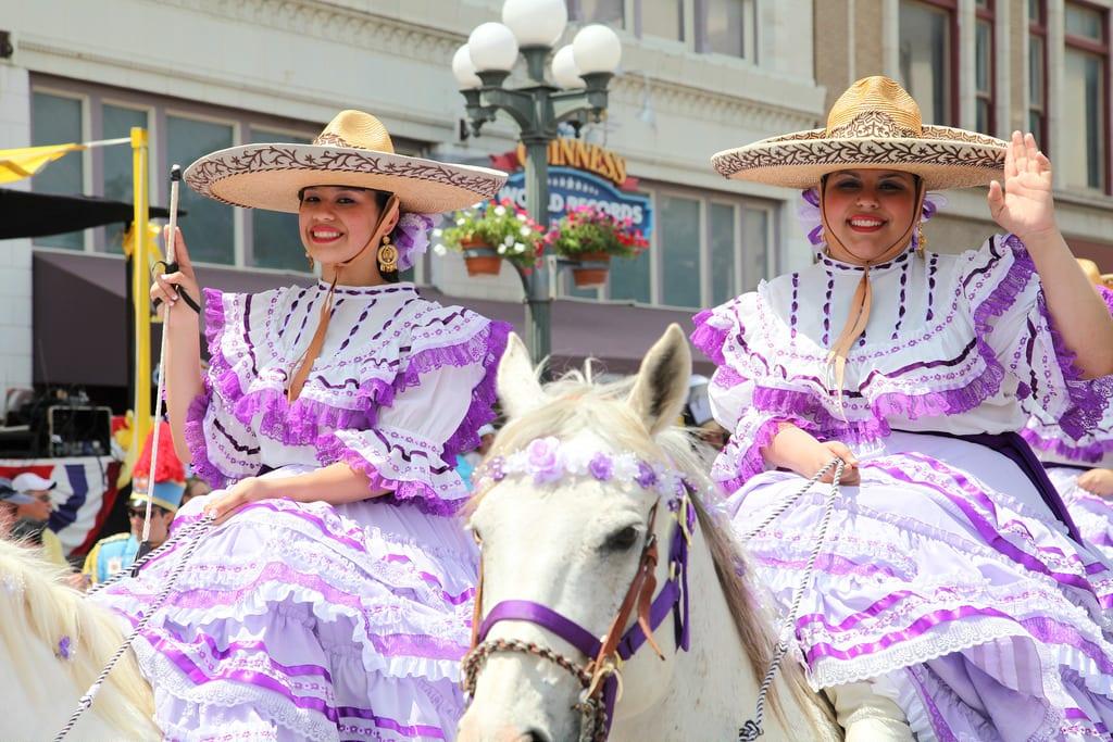two women riding horses during a San Antonio Fiesta parade