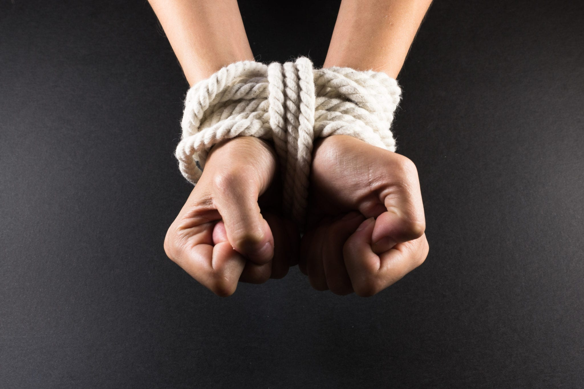 Female hands in bondage tied up with white rope.