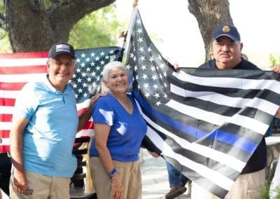 3 elderly people with back the blue flag